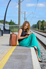 Young girl sitting on the station and reading