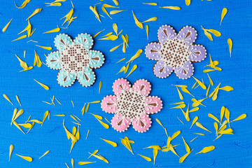 Flowers shaped cookie decorated with ornaments on blue backgroun