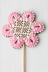 Flower shaped cookie decorated with ornaments on white wooden ba