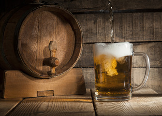 Beer barrel with beer mug on wooden background