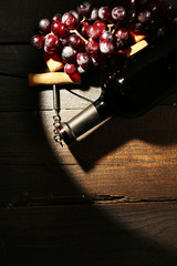 Glass bottle of wine with corkscrew and grapes in dark with