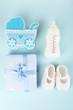 Leinwandbild Motiv Baby shoes with baby equipment on blue background