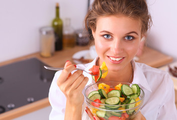 Smiling young woman in the kitchen