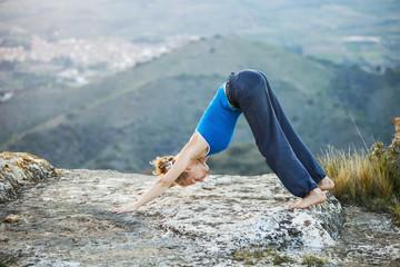 Young woman performing downward dog yoga pose
