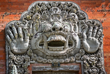 carvings depicting demons or gods above the entrance to the temp