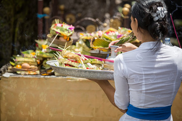 Balinese  woman carrying offering to local temple in Bali,