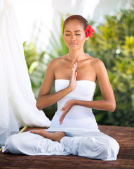 Beautiful woman practicing yoga outside