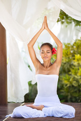 Peaceful natural woman in practicing yoga in bright nature