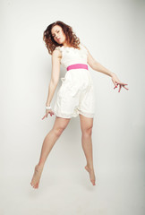 charming female in white dress jumping over grey background