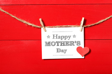Mothers day message card with heart hanging with clothespins