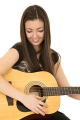 Cute girl playing her acoustic guitar looking down