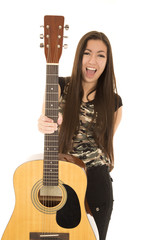 Excited female model holding out her acoustic guitar