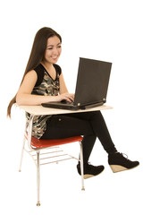 Young girl sitting at desk using computer smiling