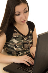 Female student typing on computer wearing camouflage shirt