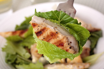 A piece of chicken caesar salad on the fork