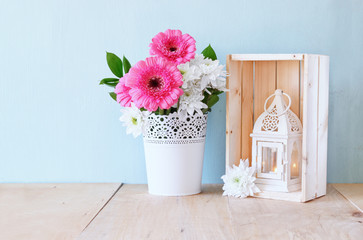 summer bouquet of flowers and vintage lantern on the wooden tabl