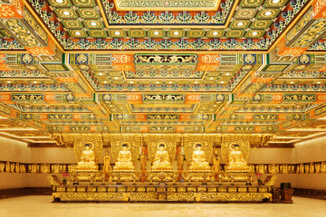 Golden Buddha statues in interior of the temple at  Po Lin Monas