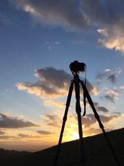camera on tripod in sunset sky