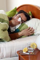 Mann niest in Taschentuch, fieberkrank im Bett