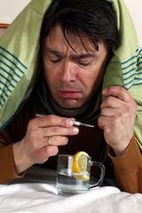 Mann im Bett schaut auf Fieberthermometer, Tee