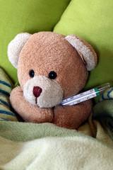 Teddybärchen mit Thermometer im Bett