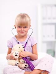 Little girl is examining her teddy bear using stethoscope