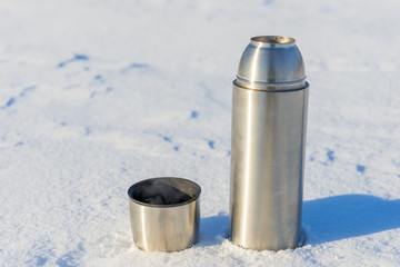 open thermos with boiling water in the snow in the winter