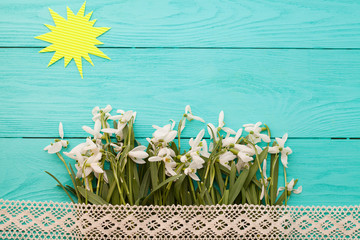 Flowers, lace and sun on blue wooden background