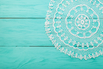 Lace doily on blue wooden background