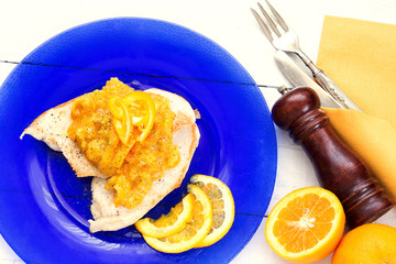 grilled chicken fillet with orange sauce over blue plate and vin