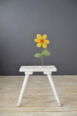 Small white wooden chair with flower  standing on the floor