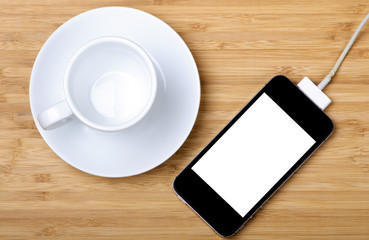 An empty coffee cup and rechargeable smartphone
