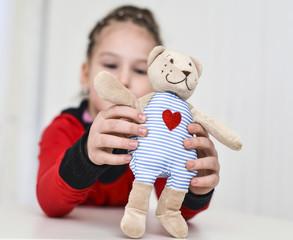 Little girl holding teddy bear sitting on the desk