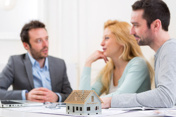 Miniature house in a desk of real estate agent with couple