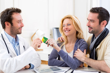Young attractive couple handling a social insurance card