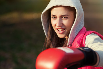 Beautiful girl in boxing gloves. Hook by fragile girl