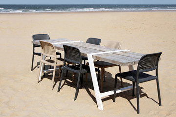 leerer tisch mit stühlen am strand
