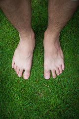 Human's foot on grass background in the park