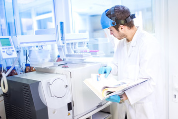 Scientist using manual for chemical computer machinery in lab