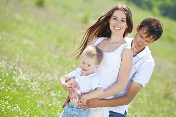 Family playing with son in the flowers field