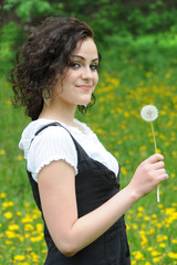 Beautiful young girl with dandelion in hand