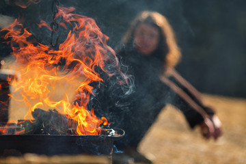 Fire flames on a grill with woman in background relaxing