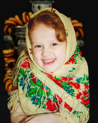 Russian smiling little girl in the national patterned scarf.
