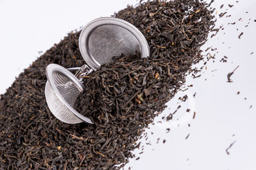 Black tea and tea strainer on white background.