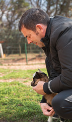 Middle-aged black-haired farmer man holding brown baby goat