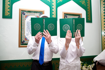 Quran in the hands of men and women