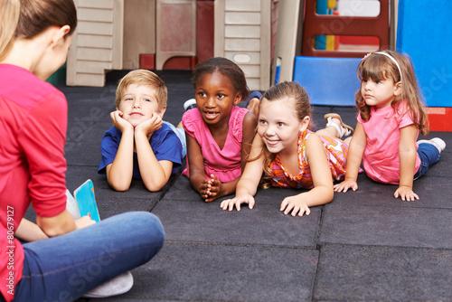 Leinwanddruck Bild Kindergärtnerin liest Kindern Buch vor