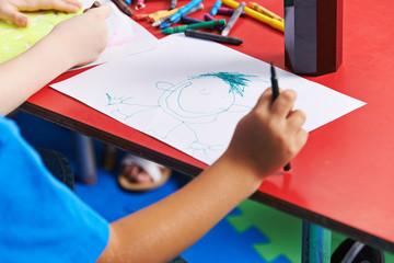Kind malt Person auf Blatt Papier