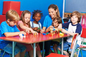Kinder und Erzieherin spielen mit Bausteinen