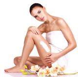 Fototapety Beautiful young woman using cream.